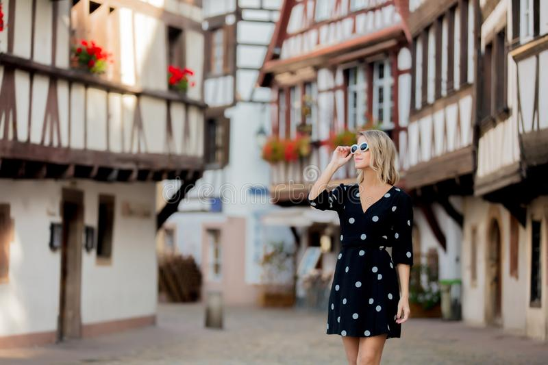黑礼服的女孩步行沿着向下街道的在史特拉斯堡 免版税库存照片