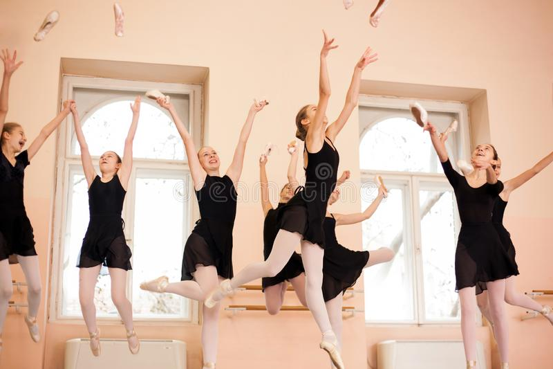 黑礼服的少年芭蕾舞女演员庆祝学期的末端中等小组  免版税图库摄影