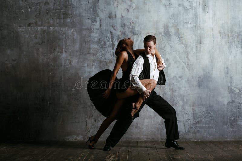 黑礼服的年轻俏丽的妇女和人跳舞探戈 免版税库存图片