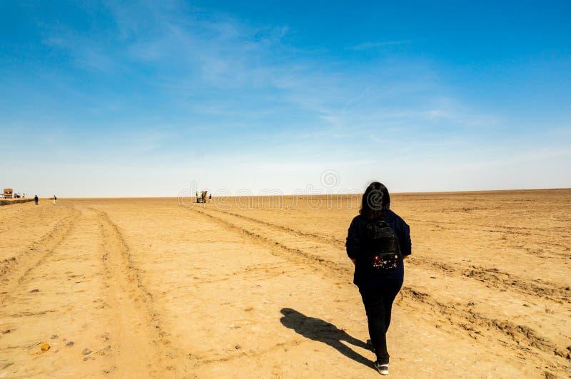 黑礼服的年轻印度女孩走在kutchh古杰雷特印度rann的  免版税库存照片