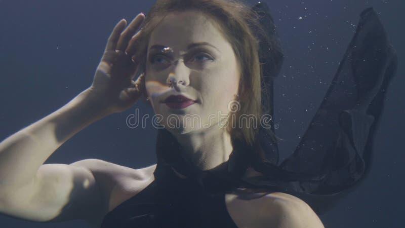 黑礼服的画象美丽的妇女游泳在水面下在黑暗的背景的 免版税图库摄影