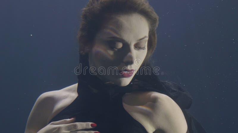 黑礼服的画象美丽的妇女游泳在水面下在黑暗的背景的 免版税库存照片