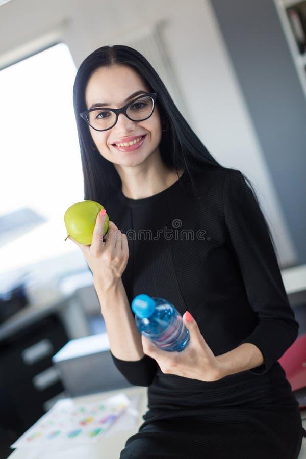 黑礼服的美丽的年轻女实业家和玻璃坐桌在办公室并且拿着绿色苹果和瓶 图库摄影