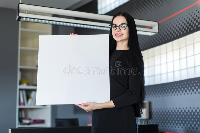 黑礼服的美丽的年轻女实业家和玻璃拿着空的海报 免版税图库摄影