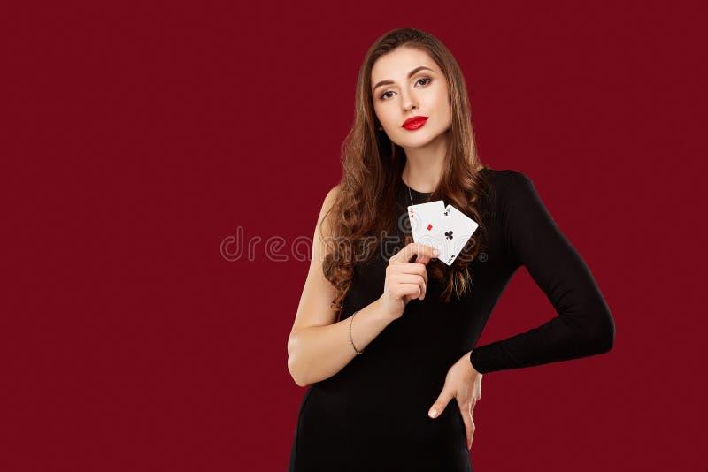 黑礼服的美丽的白种人妇女有啤牌的在赌博娱乐场拟订赌博 库存图片