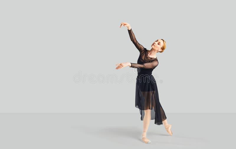 黑礼服的芭蕾舞女演员舞蹈家在灰色背景 库存照片
