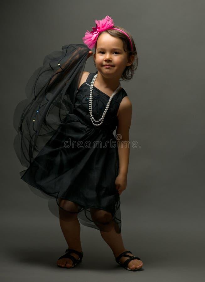 黑礼服跳舞的小逗人喜爱的女孩在灰色背景 免版税图库摄影