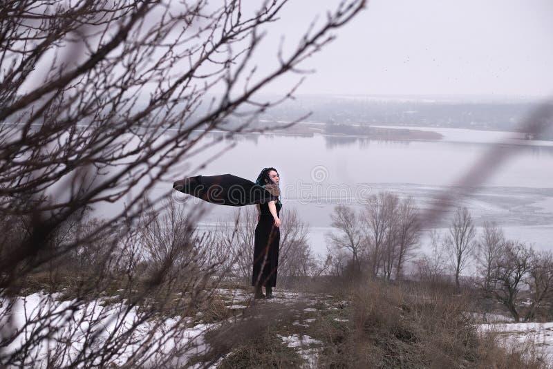 黑礼服身分的女孩在灌木和树之间的路 有一把剑的北欧海盗妇女在一件黑长的披风与 图库摄影