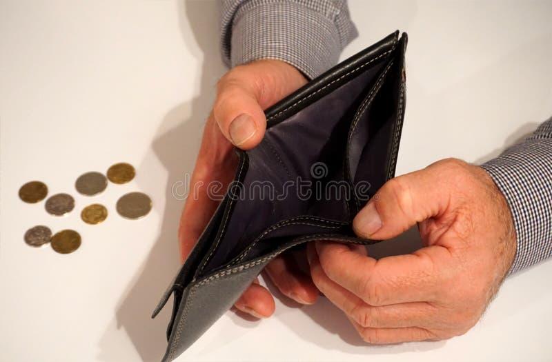 黑空的钱包在人有有些硬币的` s手上在backgrou 免版税库存图片