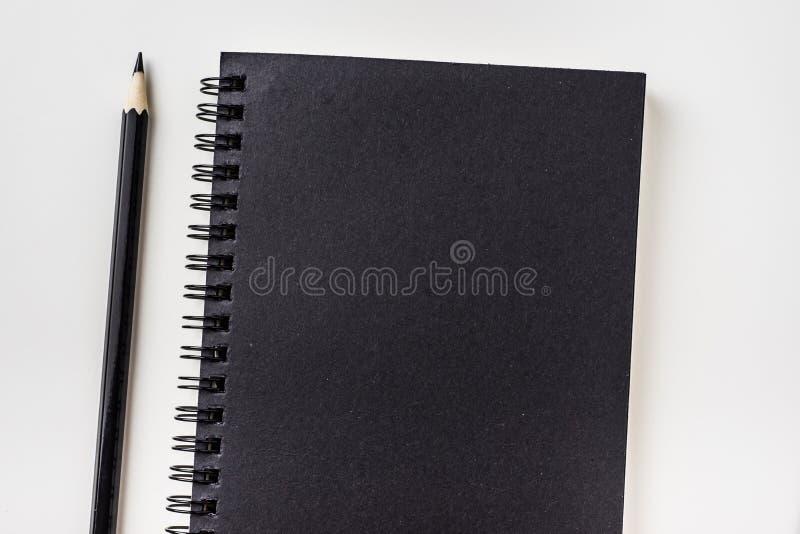 黑笔记本顶视图有黑铅笔的 免版税库存照片