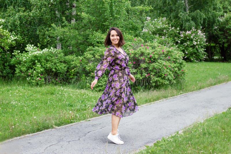 黑紫色礼服的美丽的年轻女人在有开花的淡紫色灌木的一个庭院里走 免版税库存照片