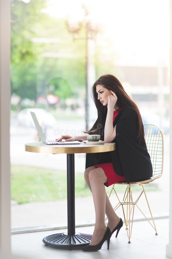 黑红色服装运转的膝上型计算机的美丽的典雅的女孩在咖啡馆的窗口后 免版税库存图片
