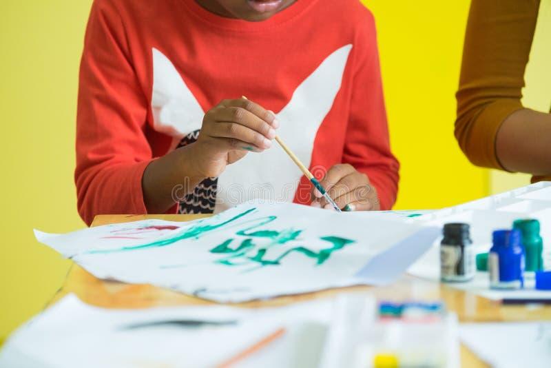 黑美国概念的关闭在学龄前幼儿园使用与颜色的刷子绘画在桌上 概念创造性的教育 库存照片