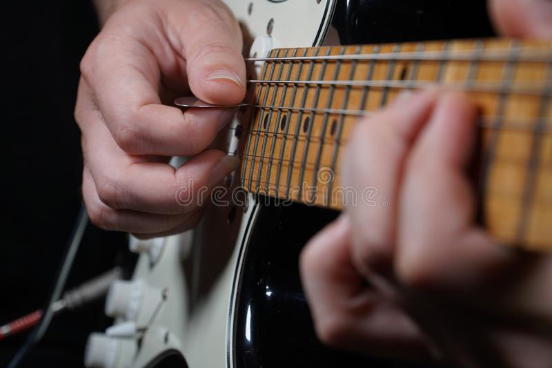 黑背景的吉他演奏员 库存照片