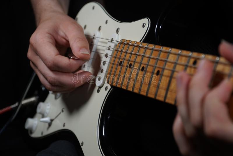 黑背景的吉他演奏员 免版税库存图片