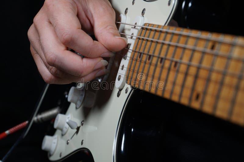 黑背景的吉他演奏员 免版税库存照片