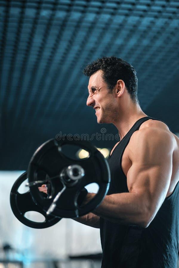 黑背景的运动员肌肉爱好健美者与杠铃 免版税图库摄影