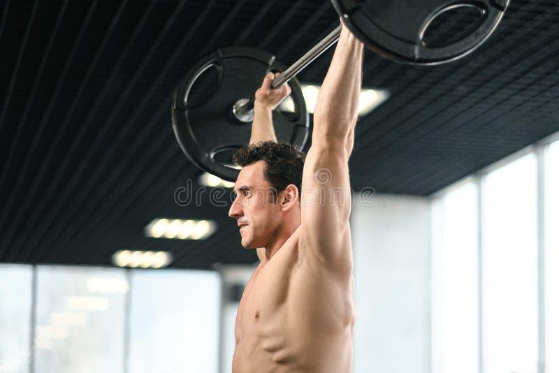 黑背景的运动员肌肉爱好健美者与杠铃 库存照片