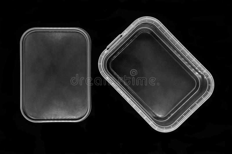 黑背景表面上分离从盒盖和隔绝的透明塑料盒底部 免版税库存照片