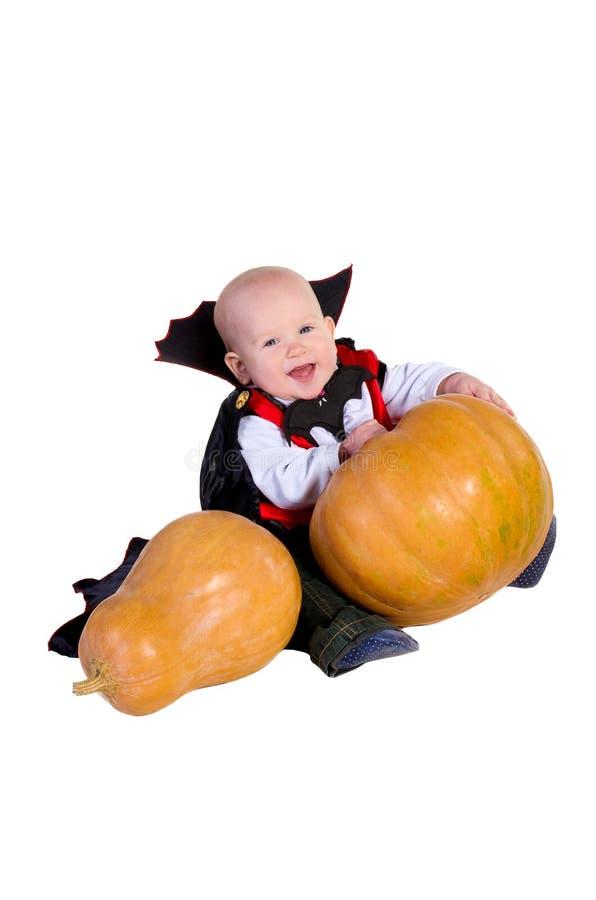 黑色万圣夜斗篷的婴孩用南瓜 库存图片