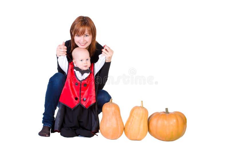 黑色万圣夜斗篷的婴孩用南瓜 免版税库存图片