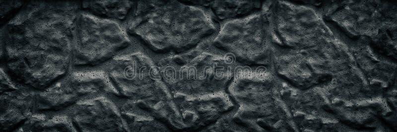 黑色变老了石墙宽纹理 黑暗的毛面长的背景 库存图片