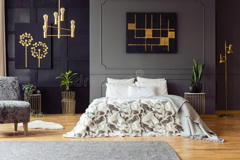 黑色和金海报在灰色墙壁上在床上在卧室内部与植物和扶手椅子 实际照片 免版税图库摄影