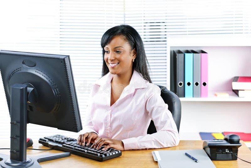 黑色女实业家服务台微笑 库存照片