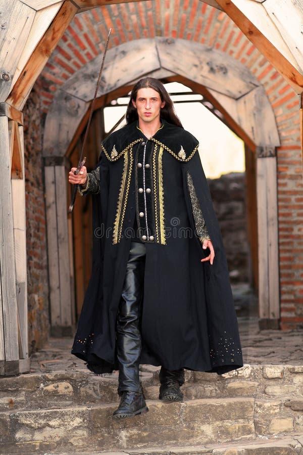 黑色披风中世纪王子军刀年轻人 免版税图库摄影