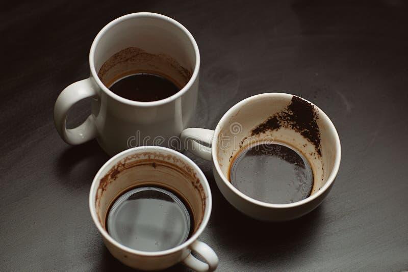 黑色木桌上的各种咖啡后,脏兮兮的多色杯子、杯子、杯子 库存照片