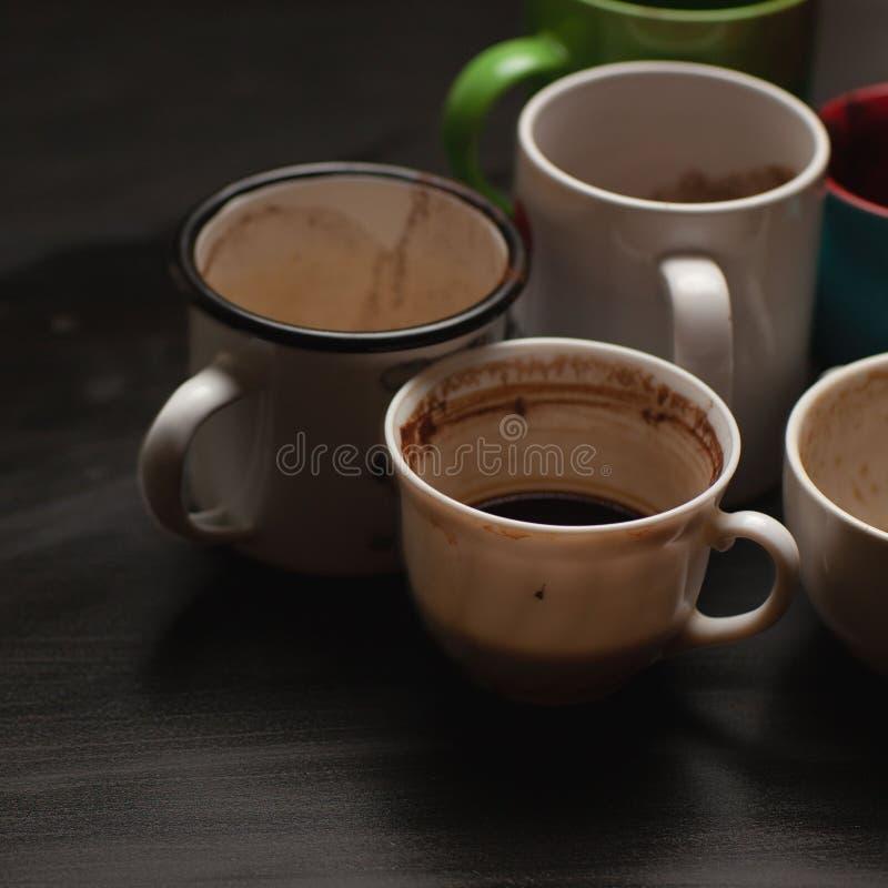 黑色木桌上的各种咖啡后,脏兮兮的多色杯子、杯子、杯子 免版税图库摄影