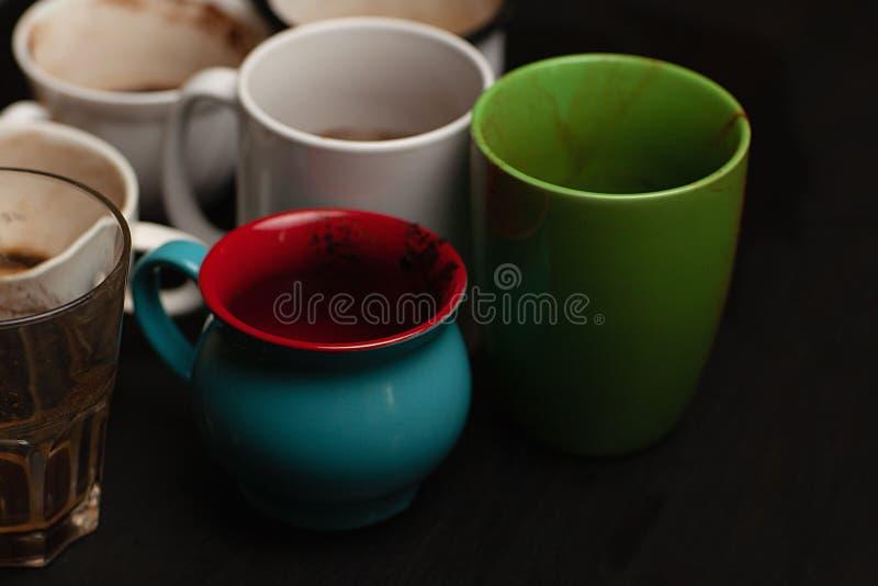 黑色木桌上的各种咖啡后,脏兮兮的多色杯子、杯子、杯子 库存图片