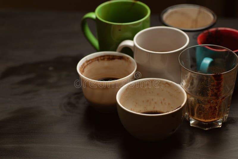黑色木桌上的各种咖啡后,脏兮兮的多色杯子、杯子、杯子 免版税库存图片