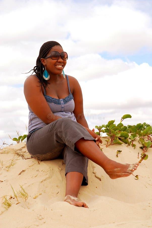 黑色沙子坐的妇女 免版税图库摄影