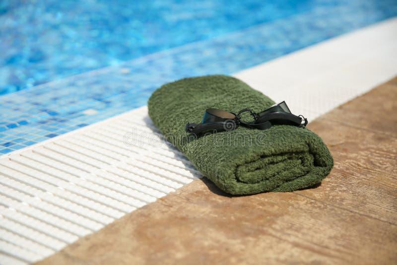黑色泳镜和泳池边缘的卷起毛巾 库存照片