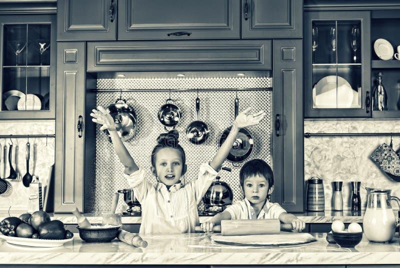 黑色白色 愉快的家庭,滑稽的孩子,准备,烘烤曲奇饼, coocing的概念 免版税库存照片