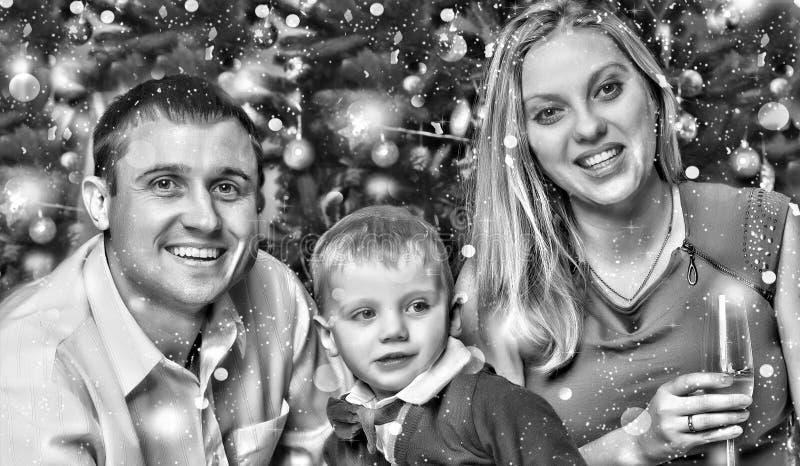黑色白色 愉快的年轻家庭集会与他们的年轻儿子的新年在圣诞树附近 库存照片