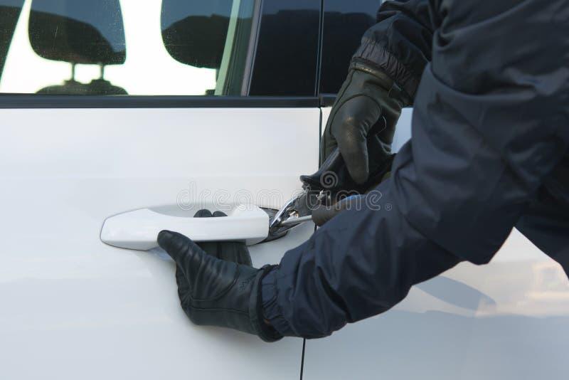 黑色的违者设法打开一辆白色汽车的门 图库摄影