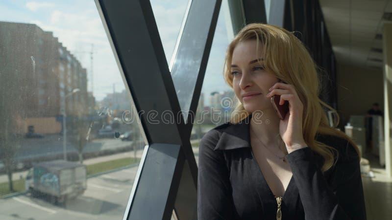 黑色的Beautisul白肤金发的女孩支持窗口和谈话在电话 免版税图库摄影