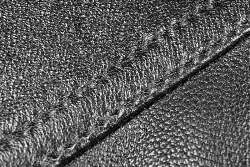 黑色穿孔了皮革纹理背景 与缝的关闭的黑皮革 发光的皮革纹理宏观射击  纹理b 图库摄影