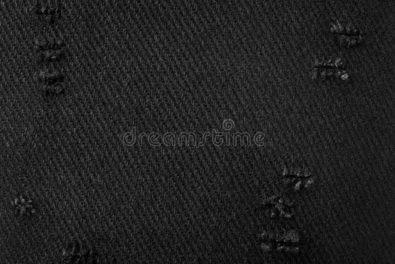 黑色织品纹理 由布料做的黑暗的材料背景 被撕毁的纺织品 库存照片