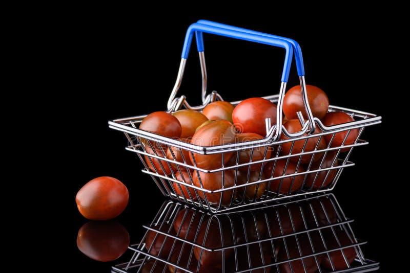 黑色背景中带有樱桃番茄把手的微型食品杂货篮 库存图片