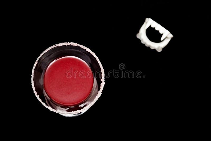 黑色背景中血腥的万圣节吸血鬼喝酒和尖牙 免版税库存图片