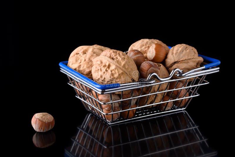黑色背景带坚果的微型食品篮 库存图片