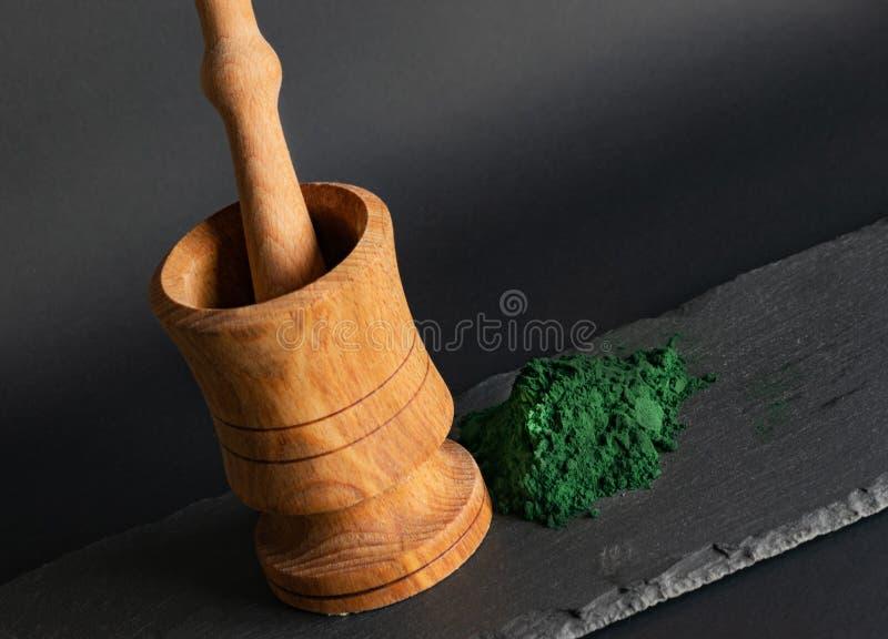 黑色背景石桌上螺旋藻粉和木桩 复制空间,天然成分补充剂 免版税库存图片