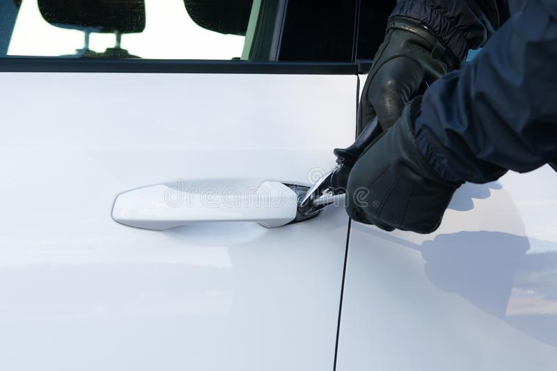 黑色衣服的一个人设法打破车门的锁在抢劫前面的 免版税库存照片