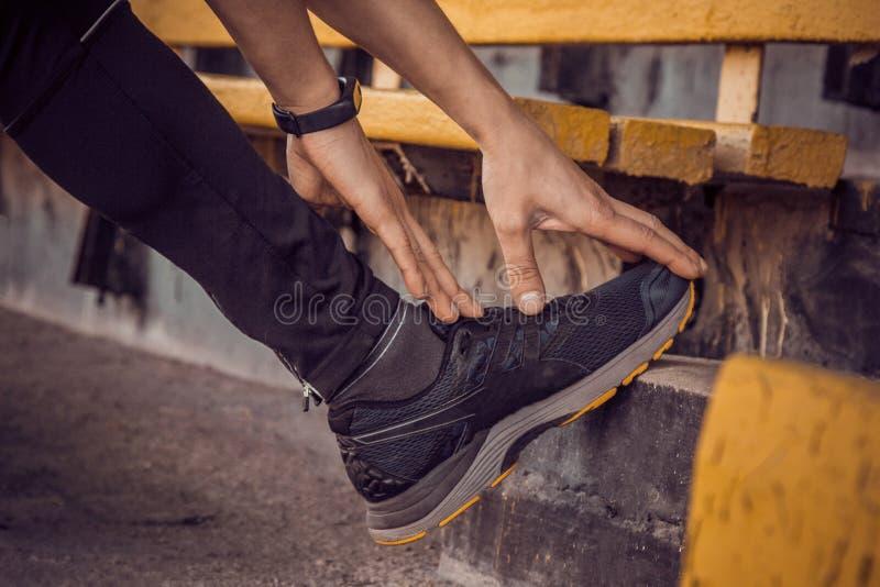 黑色衣服的一苗条年轻人在台阶行使户外 健身运动员 r ?? 免版税库存图片