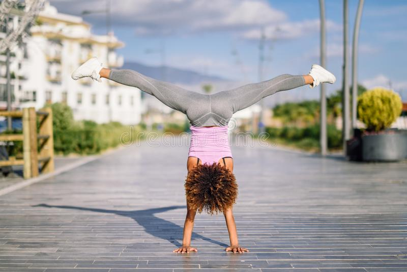 黑色适合的妇女在都市背景中的做健身杂技 免版税库存图片