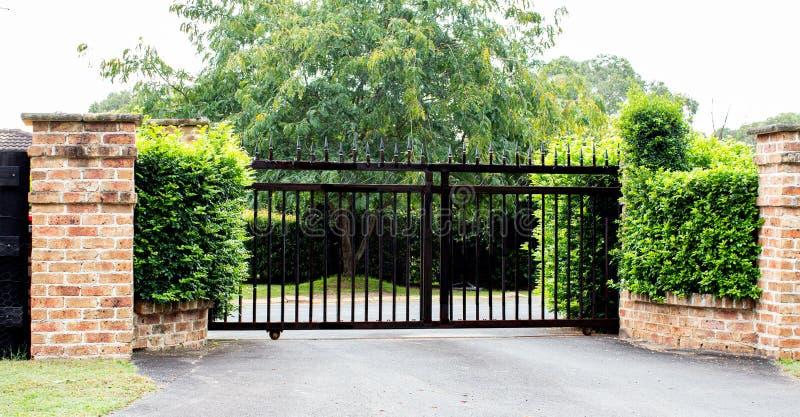 黑色金属车道入口门位于砖墙内,背景为花园灌木和树木 免版税库存照片