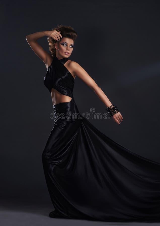 黑色长的礼服的妇女在黑暗的背景 免版税库存照片